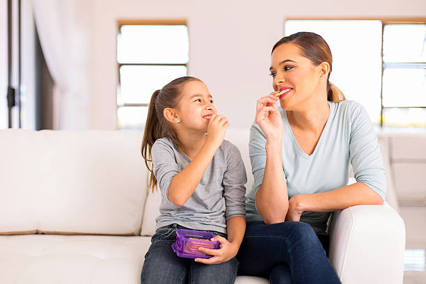 mother and daughter eating crackers stock photo