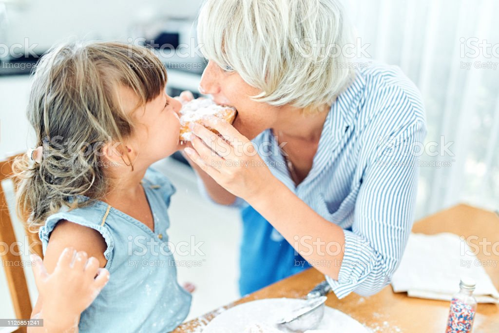 Mother and daughter eating donuts
