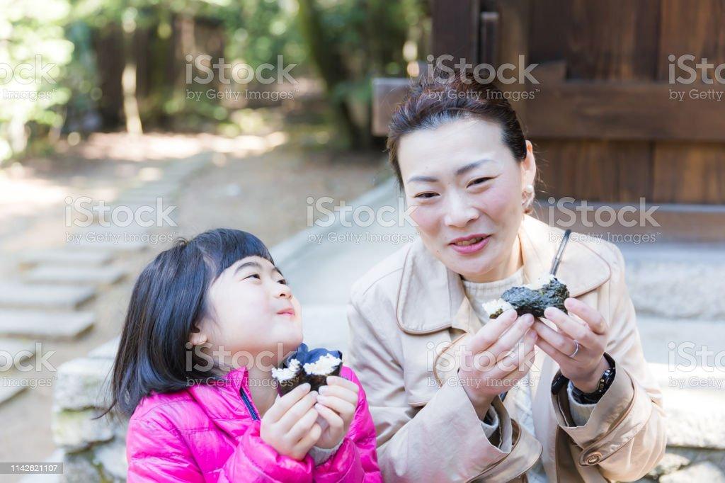 母と娘が一緒におにぎりを食べる ストックフォト