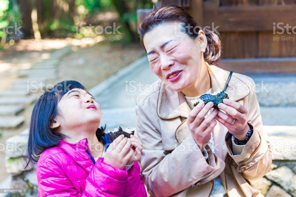 母と娘一緒におにぎりを食べて ストックフォト