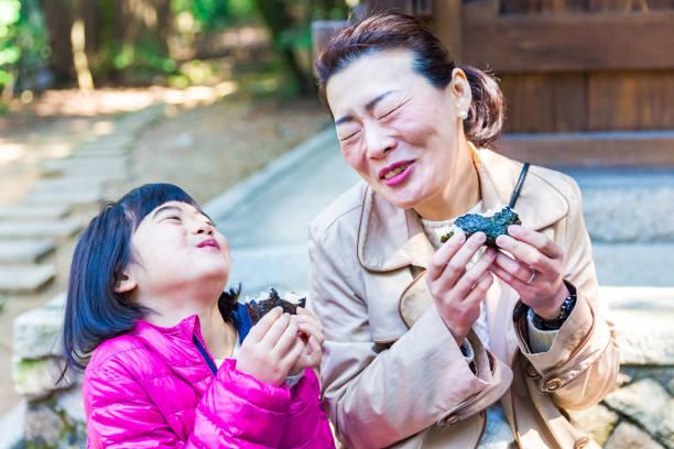 母と娘一緒におにぎりを食べて - 母娘 笑顔 日本人 ストックフォトと画像