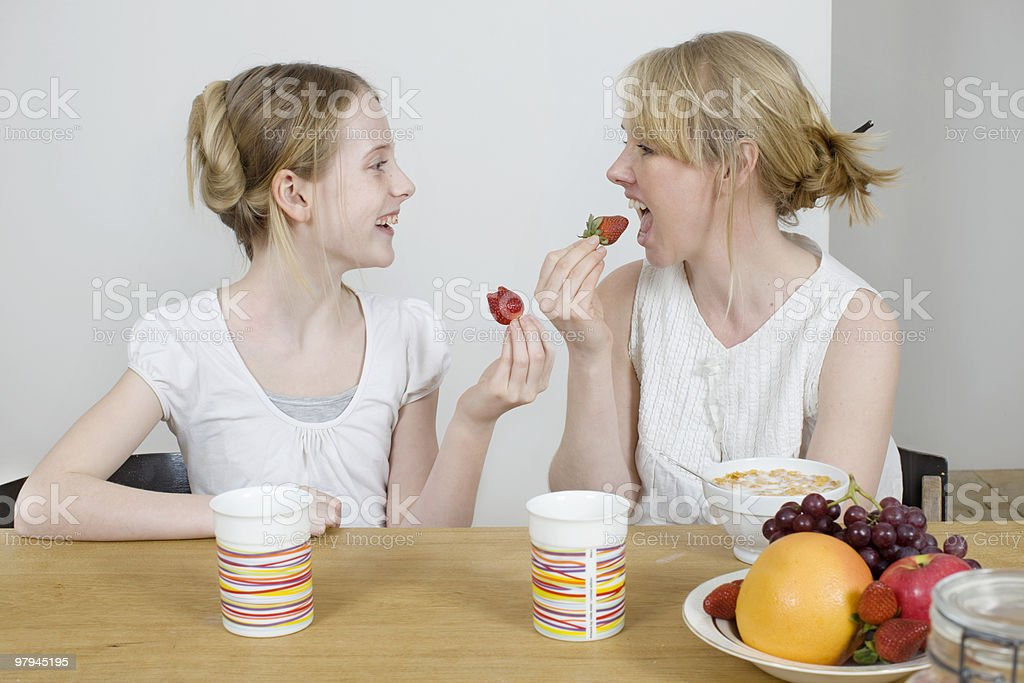 Mother and daughter eating strawberries royalty-free stock photo