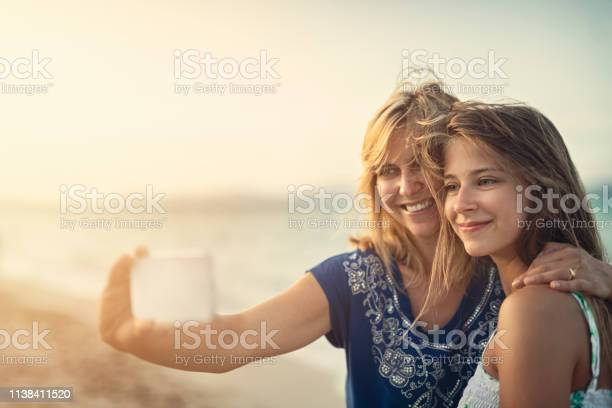 Mother and daughter embracing and taking selfies at the beach picture id1138411520?b=1&k=6&m=1138411520&s=612x612&h=gtdtudpyunwmv4u pxcot2 csq0avbnehfdf5l5zrjs=