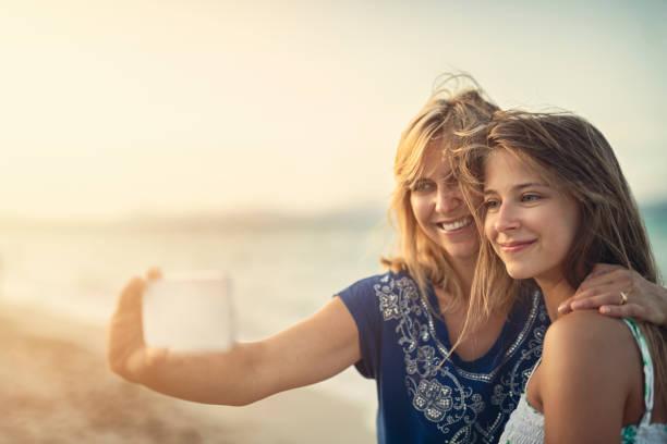 moeder en dochter omhelzen en het nemen van selfies op het strand - selfie girl stockfoto's en -beelden