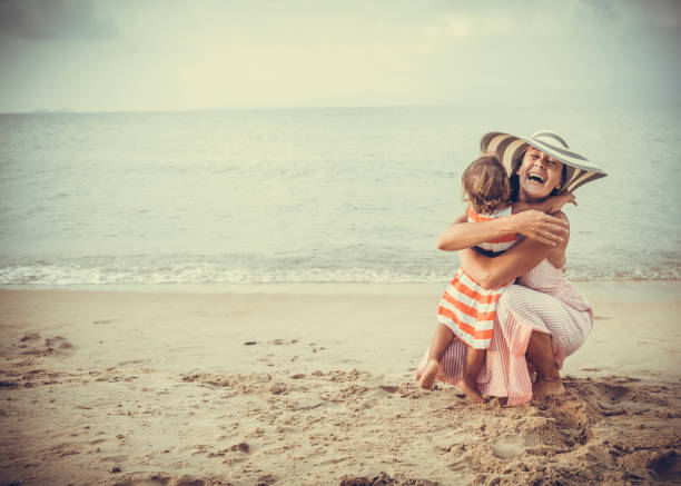 Mother and daughter embracing at the beach stock photo