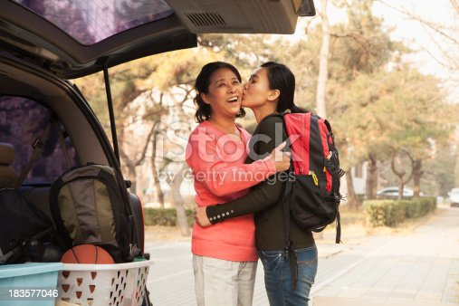 istock Mother and daughter embracing behind car on college campus 183577046