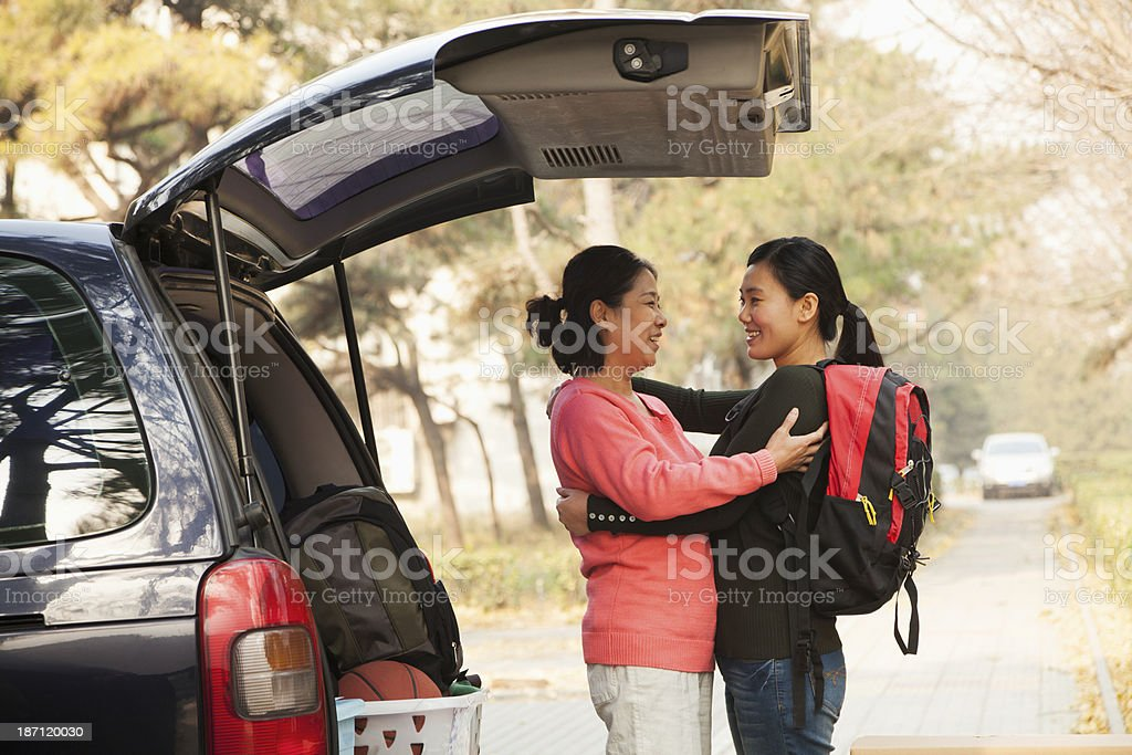 Mother and daughter embracing behind car on college campus stock photo