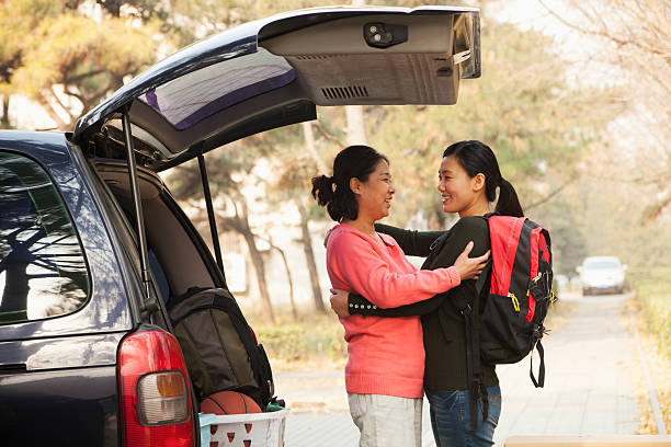 mother and daughter embracing behind car on college campus - asian travel in car stock photos and pictures