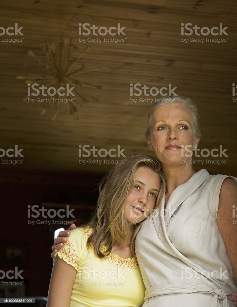 Mother and daughter (12-13) embracing, low angle view 免版稅 stock photo