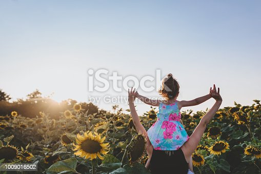 Cute and lovely toddler girl having fun in sunflower field with her mother, going through a sunflower field.