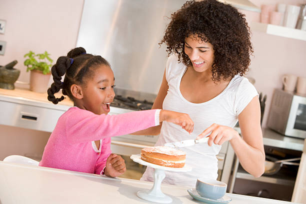 Mother and daughter enjoy icing a cake together Mother and daughter in kitchen icing a cake together smiling decorating a cake stock pictures, royalty-free photos & images