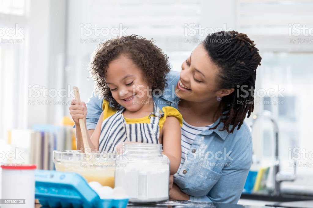 A mid adult mother and her preschool age daughter smile as they stand...