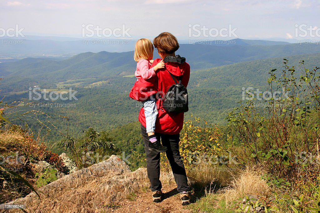 Mother and daughter enjoy the view from mountain after hike royalty-free stock photo