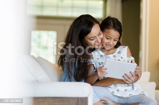 A mid adult mother holds her elementary age daughter in her lap.  They look down at a digital tablet as they sit in their living room together.