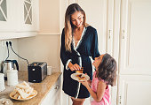 istock Mother and daughter enjoying breakfast 877083406