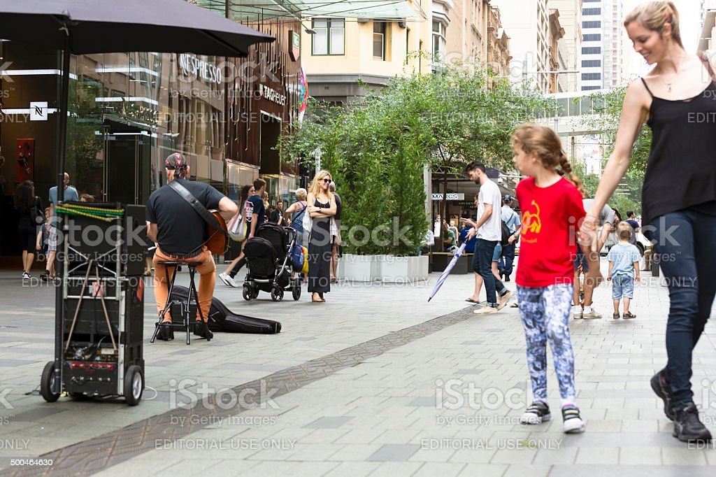 Mother and daughter enjoying local musician performing on Pitt Street stock photo