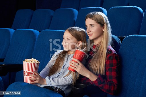 istock Mother and daughter enjoying movie in movie theatre. 1147577414