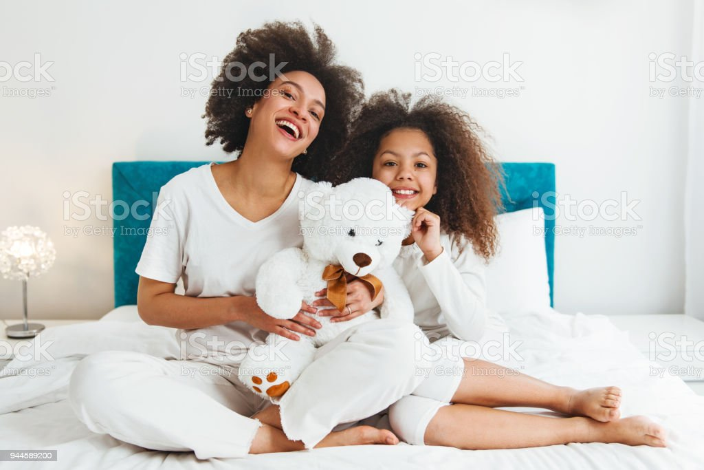 Mother and daughter enjoying on the bed, happy, smiling stock photo