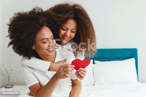 istock Mother and daughter enjoying on the bed, holding a heart 944590500