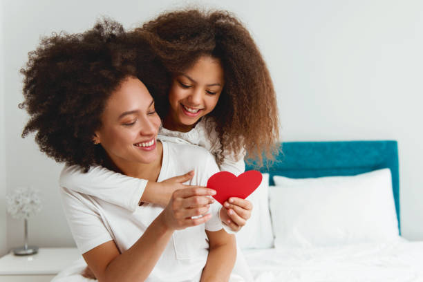 mother and daughter enjoying on the bed, holding a heart - mother stock photos and pictures