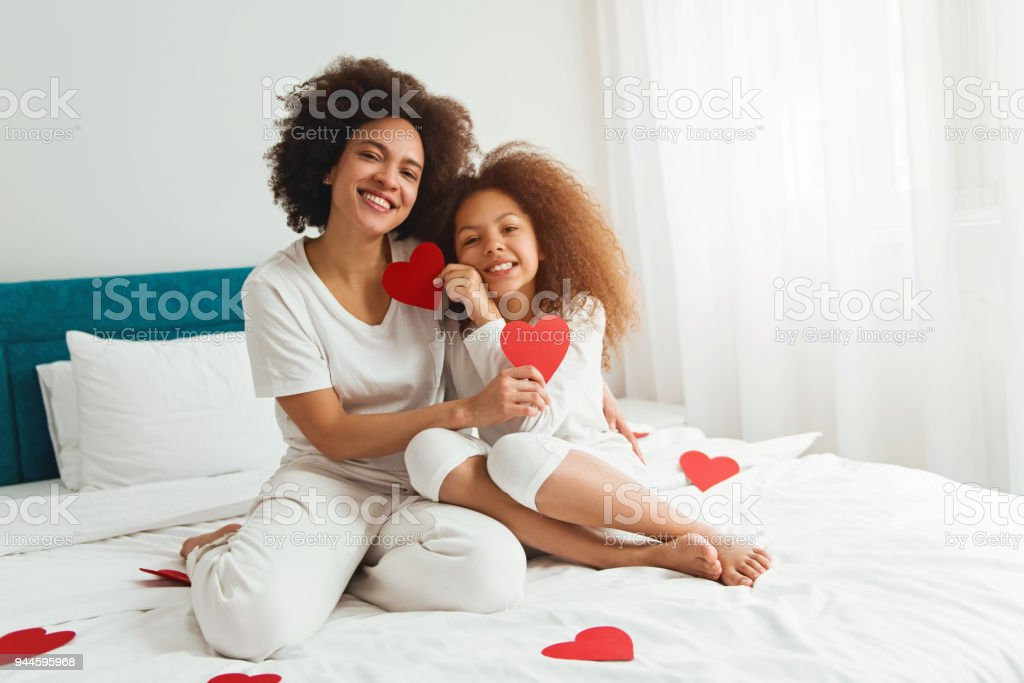 Mother and daughter enjoying on the bed, holding a heart stock photo