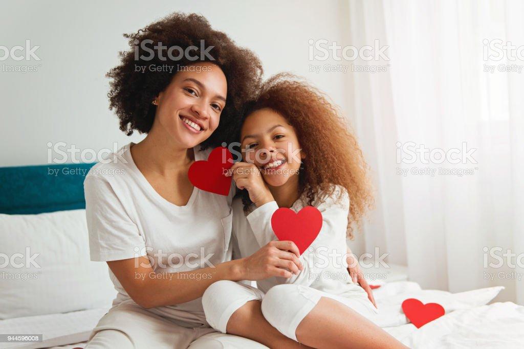 Mutter und Tochter genießen auf dem Bett, hält ein Herz – Foto