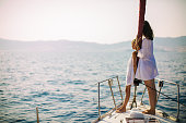 Mother and daughter standing on yacht bow on deck while sailing over nice calm sea. They both wearing white summer dress.