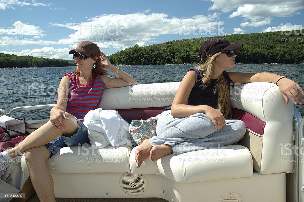 Mother And Daughter Enjoying Pontoon Boat On Lake stock photo