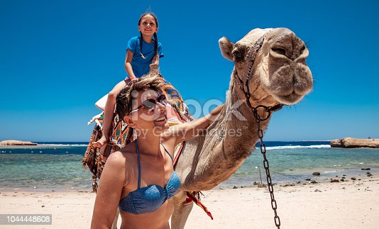 883177796istockphoto Mother and Daughter Enjoying Riding a Camel in Egyot 1044448608