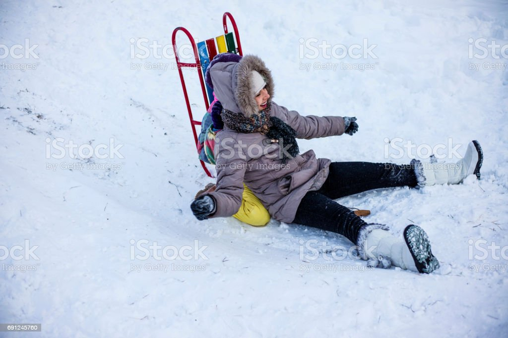 Mother and daughter enjoying sledge ride stock photo