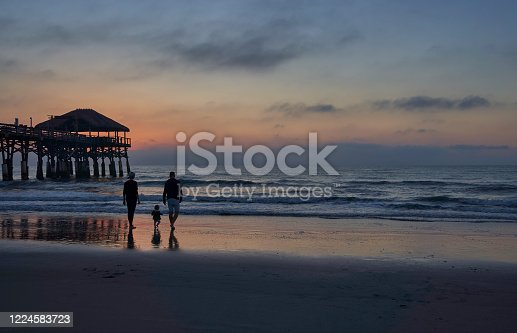 Mother and daughter enjoying the beach and sunrise at the Cocoa Beach Pier in Cocoa Beach,  Central Florida USA.