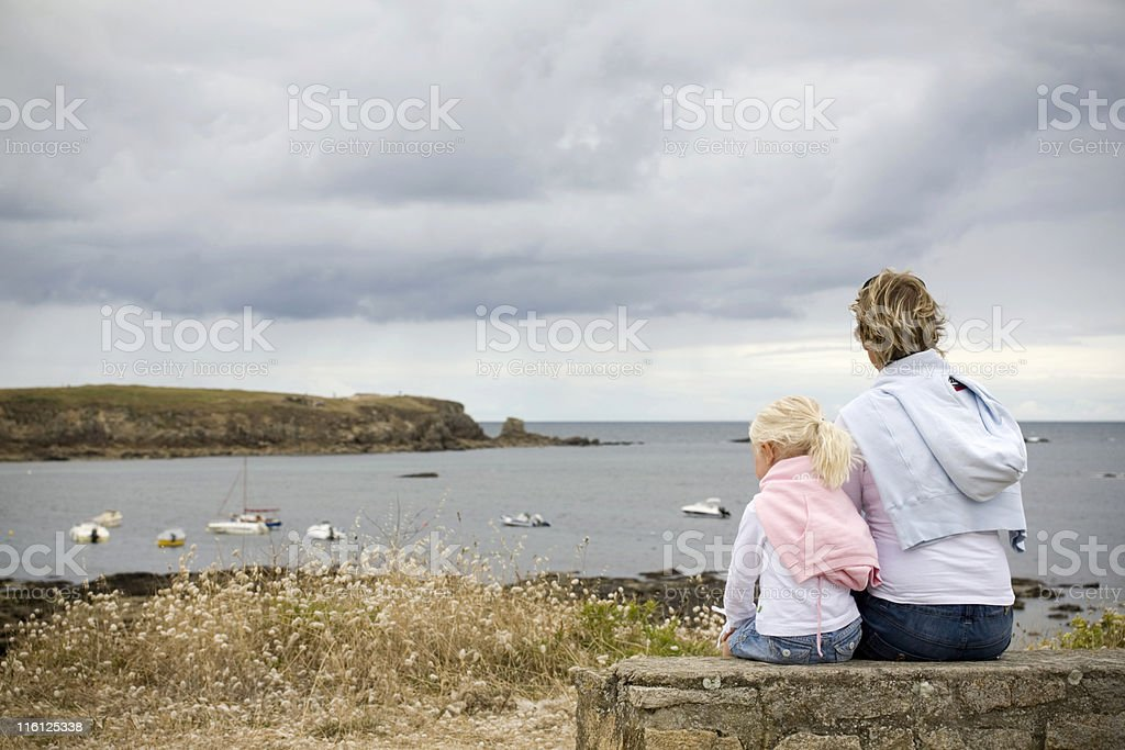 mother and daughter enjoying the coastal view stock photo