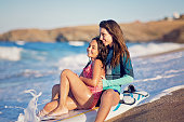 Mother and daughter enjoying the view on the beach