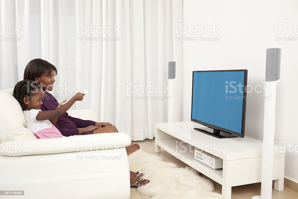 Mother and daughter enjoying watching TV. stock photo