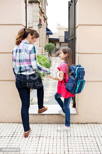 istock Mother and daughter entering school gate 996963978