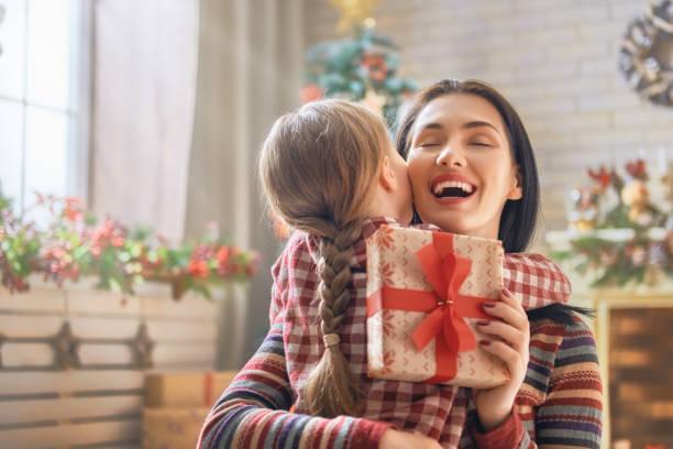 mutter und tochter austausch von geschenken - geschenke eltern weihnachten stock-fotos und bilder