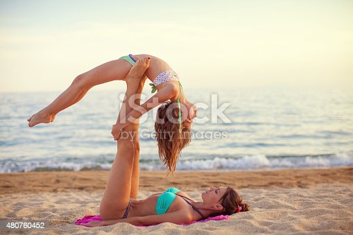 istock Mother and daughter exercising on the beach 480760452
