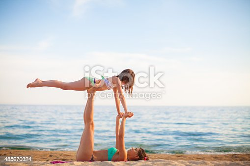 istock Mother and daughter exercising on the beach 485670324