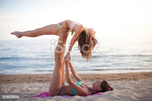 istock Mother and daughter exercising on the beach 526829204