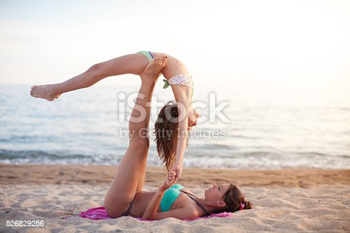 istock Mother and daughter exercising on the beach 526829256