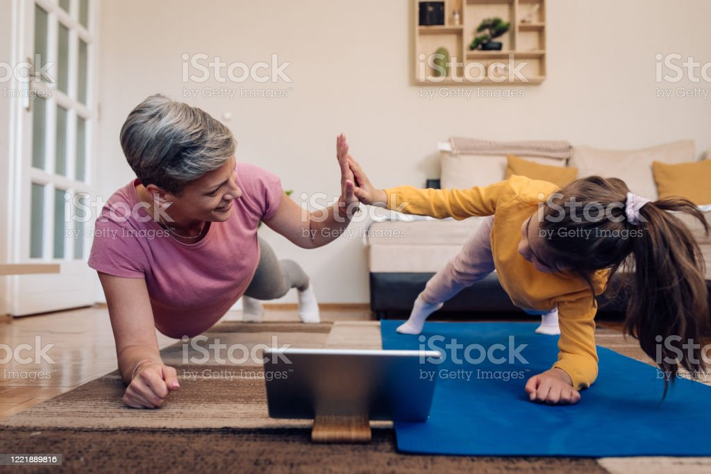 Mother and daughter exercising watching an online training Little girl and her mother exercising at home. Active Lifestyle Stock Photo