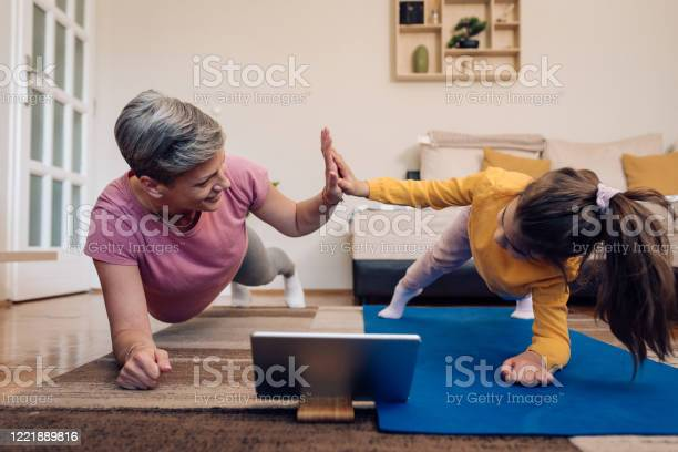 Mother And Daughter Exercising Watching An Online Training Stock Photo - Download Image Now