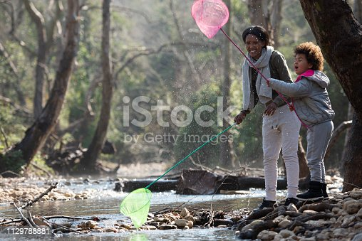 Mother and daughter fishing using a fishing net. Young African mother with her 5 years old girl standing near the river edge and trying to fish.