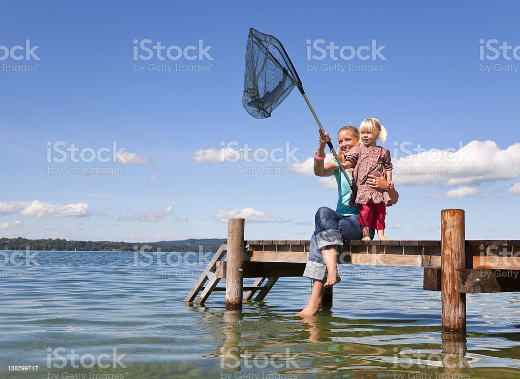 Mother and daughter fishing with net stock photo