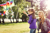 Mother is flying a kite with her daughter in nature, in windy conditions. Genuine emotions, AdobeRGB profile.