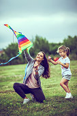 Mother and daughter flying kite outdoors