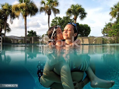 istock Mother and daughter fun in swimming pool 1193863079