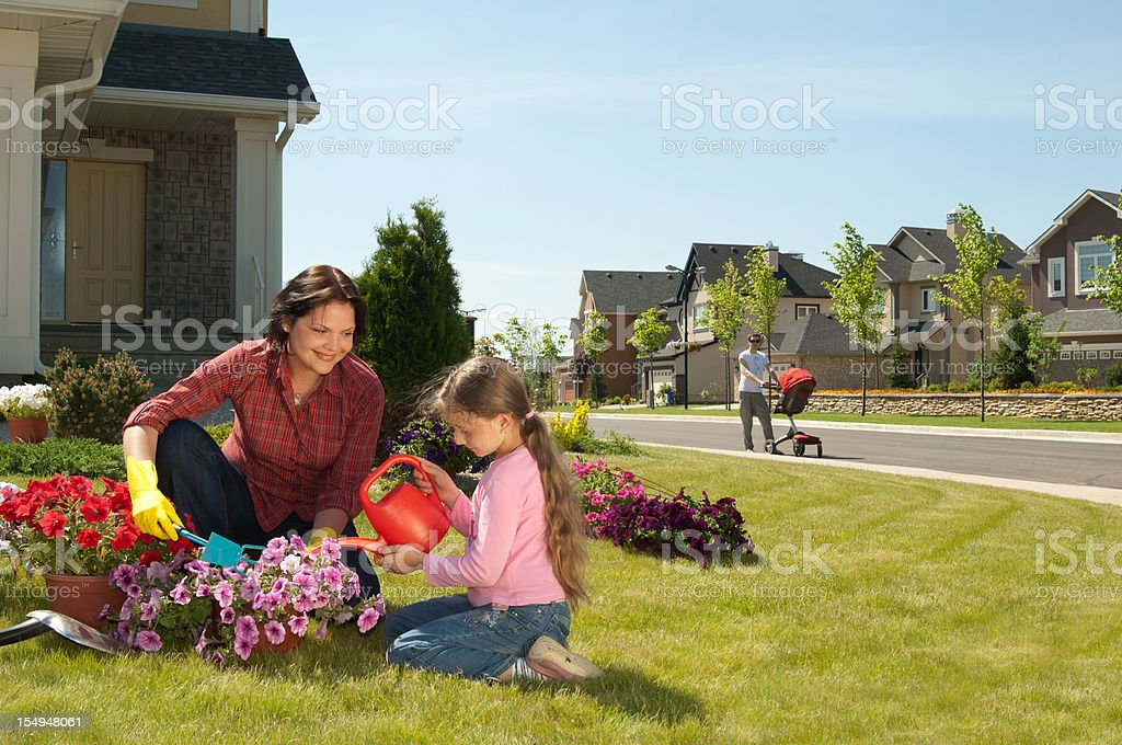 Mother and daughter gardening while father walks with baby stock photo