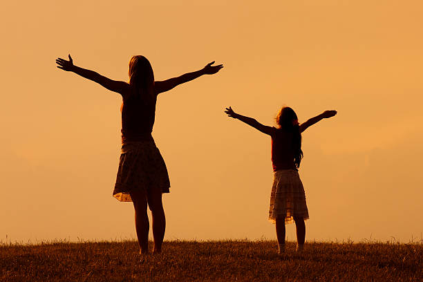 Mother and daughter greeting the sunset – Foto