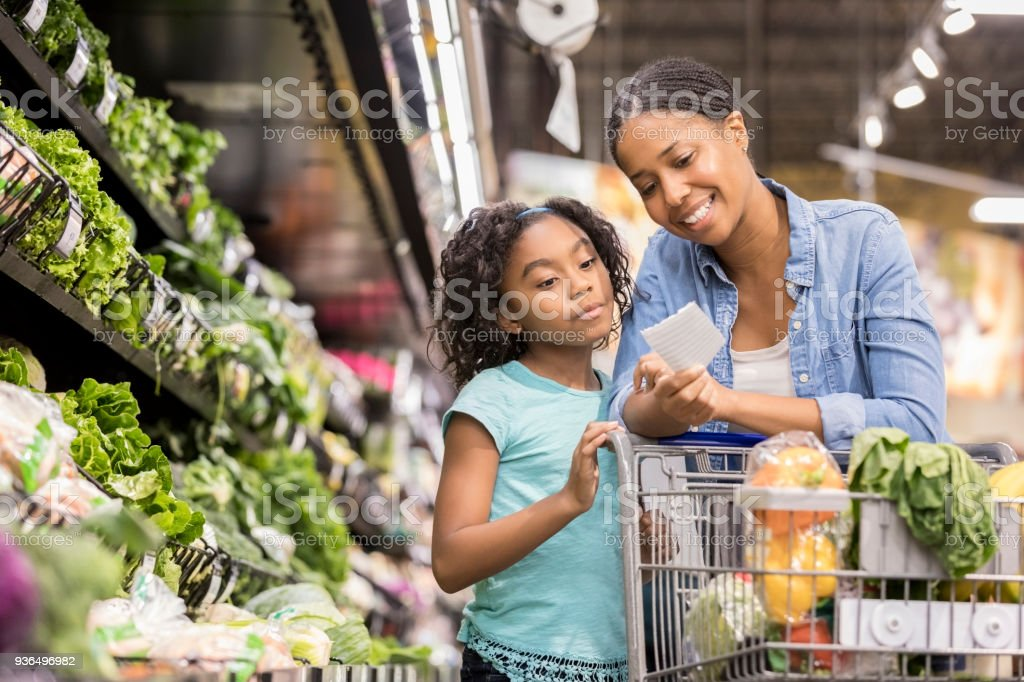 Mother and daughter grocery shop together using list stock photo